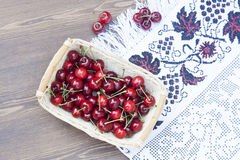 Fresh cherries on embroidered towel. And wooden table royalty free stock images