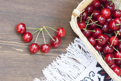Fresh cherries. On embroidered towel and wooden table royalty free stock photo