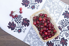 Fresh cherries on embroidered towel. In wooden table stock image