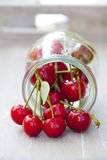 Fresh cherries in front of a preserving jar Royalty Free Stock Images