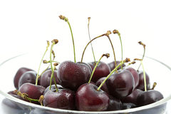 Fresh cherries in a glass bowl. On white background Stock Photos