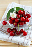 Fresh cherries in a glass cup with jasmine flower Royalty Free Stock Images