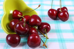 Fresh cherries in green bowl on checkered tablecloth, healthy food Stock Images