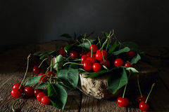 Fresh cherries with leaves on a piece of wood. Fresh cherries with leaves on an old piece of wood in the shed. Free space for an inscription stock images