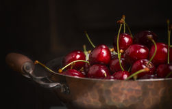 Fresh cherries in old copper pan on dark background, close up Royalty Free Stock Photos