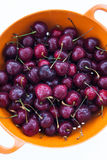 Fresh cherries  in the orange colander Stock Images