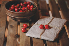 Fresh cherries on plate with wrapped gift on wooden table. Royalty Free Stock Photo