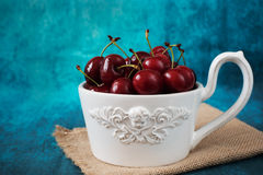 Fresh cherries in a white bowl, a large cup. Fresh fruits, fruit salad. Blue background. Rustic style Royalty Free Stock Photography
