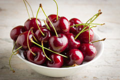 Fresh cherries in a white bowl. On wooden background Royalty Free Stock Images