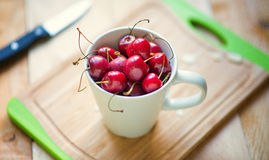 Fresh cherries in a white cup. Fresh raw organic red cherries in a white cup ready to be eaten Stock Images