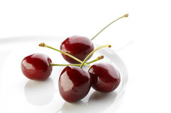 Fresh cherries on white plate Royalty Free Stock Photo