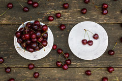 Fresh cherries in white vintage bowl on old wooden table. Ripe berries on background, summer day. Top view Royalty Free Stock Photos