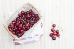 Fresh cherries in wicker basket. On lighten makisu royalty free stock photography