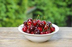 Fresh cherries in wicker basket royalty free stock photos