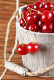 Fresh cherries in a wood bucket. Fresh cherries with water drops in a wood bucket Stock Image