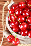 Fresh cherries in a wood bucket. Fresh cherries with water drops in a wood bucket Stock Photo