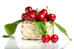 Fresh cherry berries in a basket. Fresh cherry berries with green leaves and drops in a basket isolated on white Royalty Free Stock Photography