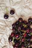 Fresh cherry berries lie on rumpled parchment paper. Concept of Royalty Free Stock Images