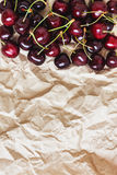 Fresh cherry berries lie on rumpled parchment paper. Concept of Royalty Free Stock Image