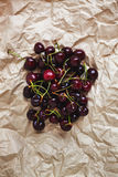 Fresh cherry berries lie on rumpled parchment paper. Concept of Stock Photos