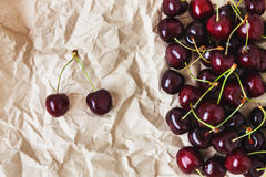 Fresh cherry berries lie on rumpled parchment paper. Concept of Royalty Free Stock Photography