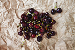 Fresh cherry berries lie on rumpled parchment paper. Concept of Royalty Free Stock Photo