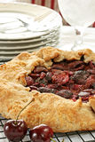 Fresh Cherry Crostata - vertical. Fresh cherry crostata with two cherries in foreground; dishes and water glass in background Royalty Free Stock Photos