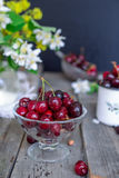 Fresh cherry fruit in glass vase, other dishes with berries and jar with jasmine and wildflowers on the old wooden table. Soft sel. Ective focus. Summer rustic stock photos