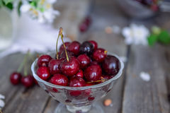 Fresh cherry fruit in glass vase, other dishes with berries and jar with jasmine and wildflowers on the old wooden table. Soft sel. Ective focus. Summer rustic stock photography