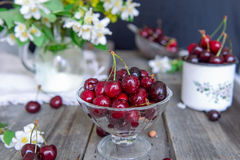 Fresh cherry fruit in glass vase, other dishes with berries and jar with jasmine and wildflowers on the old wooden table. Soft sel. Ective focus. Summer rustic stock photo