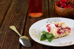 Fresh cherry pie on white plate with golden motif. Horizontal photo of fresh cherry pie on white plate with several herb leaves. Spoon, bottle and bowl with royalty free stock images