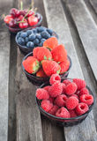 Fresh cherry, strawberry, blueberry and raspberry. In a bowls on wooden table Royalty Free Stock Photography