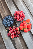 Fresh cherry, strawberry, blueberry and raspberry. In a bowls on wooden table Stock Photography