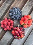 Fresh cherry, strawberry, blueberry and raspberry. In a bowls on wooden table Stock Photos