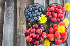 Fresh cherry, strawberry, blueberry and raspberry. On wooden table, copy space Stock Photo