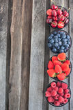 Fresh cherry, strawberry, blueberry and raspberry. On wooden table, copy space Stock Photos