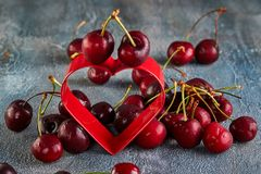 Fresh Cherry or sweet cherry with water drops with a red heart. Concept for valentines day stock photo