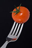 Fresh Cherry Tomato on a Fork. A fresh cherry tomato on a silver fork, shot against a black background Stock Photo