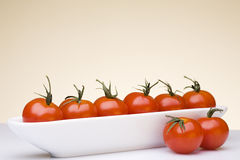 Fresh cherry tomatoes. Fresh cherry tomatoes in a white bowl set against a yellow background Stock Photography