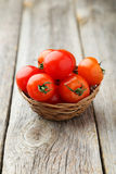 Fresh cherry tomatoes in basket on a grey wooden background Stock Photos