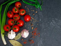 Fresh cherry tomatoes on black background with onion and garlic. Top view with copy space Royalty Free Stock Photos