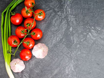 Fresh cherry tomatoes on black background with onion and garlic. Top view with copy space Royalty Free Stock Photo
