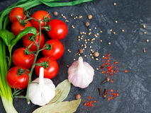 Fresh cherry tomatoes on black background with onion and garlic. Top view with copy space Royalty Free Stock Image