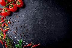 Fresh cherry tomatoes on a black background with spices with slate plate. Top view with copy space. Fresh cherry tomatoes on a black background with spices with stock image