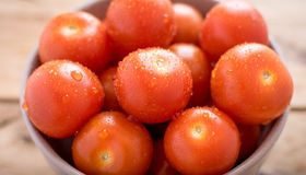 Fresh cherry tomatoes in bowl on wooden background Royalty Free Stock Photos