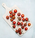 Fresh cherry tomatoes on a branch on a white cutting board wooden rustic background top view Royalty Free Stock Image
