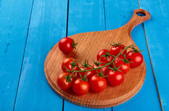 Fresh cherry tomatoes on a branch on a wooden cutting board on blue wooden rustic background top view Royalty Free Stock Photo