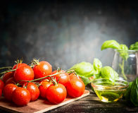 Fresh cherry tomatoes bunch with basil and oil on dark rustic background, side view Royalty Free Stock Images