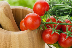 Fresh cherry tomatoes closeup. With potherb and pounder Stock Image