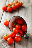 Fresh cherry tomatoes in cup on the grey wooden background Royalty Free Stock Photo